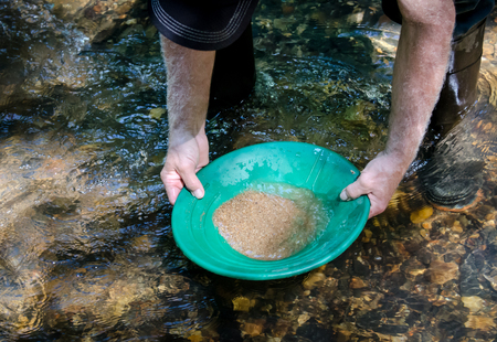 Gold pan filled with material.  Prospecting for gold and gemstones. Fun and adventure enjoying recreational activity.