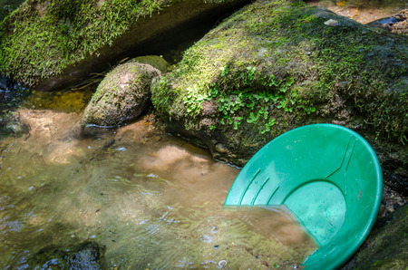 Gold pan resting in mineral rich riverbed material. Fun and adventure enjoying the recreational outdoor activity of panning for gold, prospecting for gemstones. 版權商用圖片 - 85706506