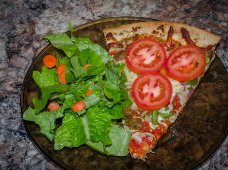 Fresh baked pizza with tomato slices, served with crisp green salad. Standard-Bild - 93298080