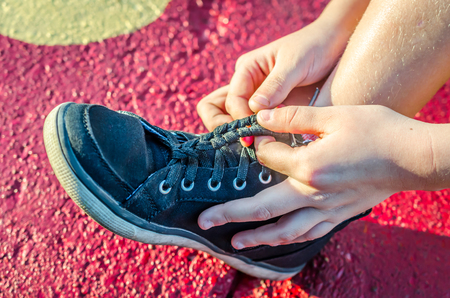 Tying shoelace into braid. Fashion and style in this unique way to tie tennis shoe laces to keep from hanging loose.