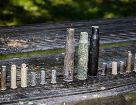 Empty gun ammunition shell casings. Variety of sizes of used weapon shell casings.