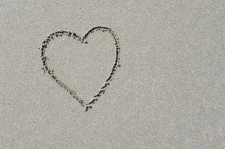 Heart shape etched into ocean beach sand. Symbol of love and romance at the beach.