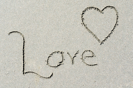 Love and heart shape written in ocean beach sand. Romance at seaside setting. Stock Photo