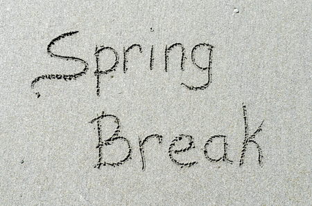 Spring break message written in ocean beach sands. Fun and adventure during this springtime tradition. Stock Photo