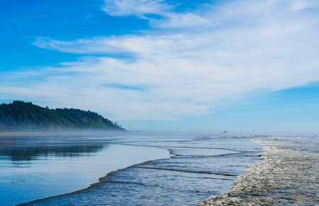 Pacific Northwest ocean beach scene with waves splashing onshore. Distant mountain hills reflecting in wet coastal sands.
