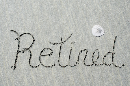 Retired message written in ocean beach sands. Concept of enjoying retirement relaxing at the beach. Stock Photo