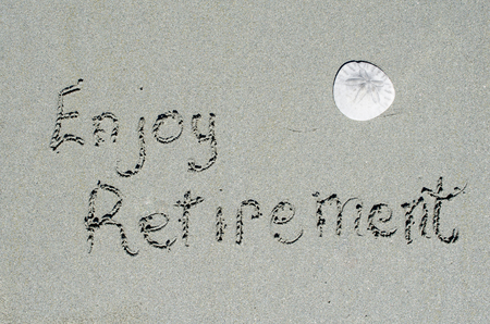 Enjoy retirement message written in ocean beach sands. Concept of celebrating retirement.