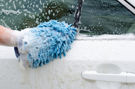 Car wash with soap suds. Hand washing car with cleaner, mitt and soap bubbles.