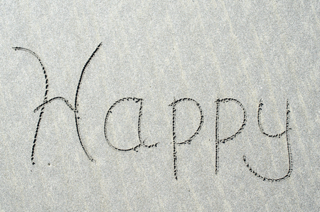 Happy written in ocean beach sands. Fun, adventure and happiness found at ocean beaches.
