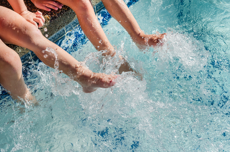 Childrens feet splashing in sparkling blue pool water. Fun activity for children in summertime sunshine.