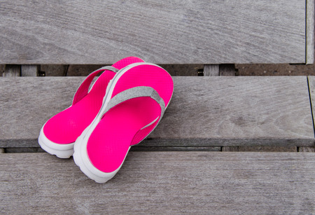 Hot pink and gray sandals resting on wooden beach bench. Conceptual image of fun in the summertime sunshine. Stock Photo