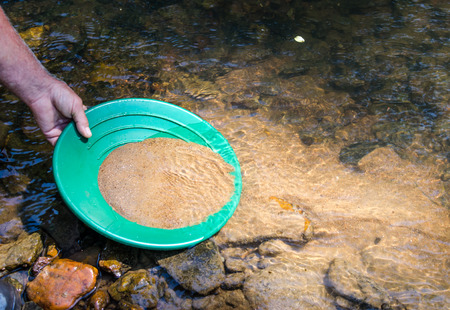 Panning for gold in mineral rich stream. Fun and adventure in this outdoor recreational activity of prospecting for gold and gem stones. Stock Photo