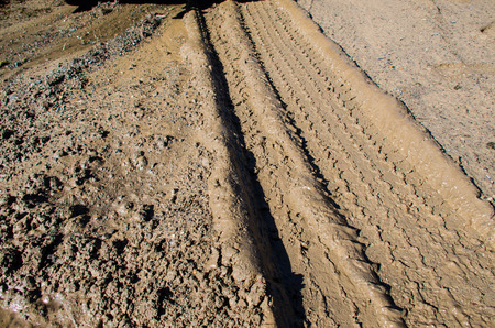 Tire tracks in the mud. Wet dirt road with vehicle imprints of tire tracks.