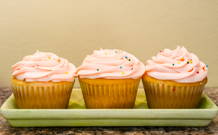 Sweet butter cream frosting swirled on top of home baked cupcakes. Colorful candy sprinkles on top. Stock Photo