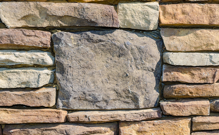 Stone Rock wall with large center stone for backdrop. Excellent rustic background scene with space for text. Beautiful rustic colorful textured outdoor stone wall. Standard-Bild - 114070579