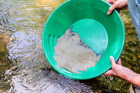 Panning for gold in mineral rich stream. Fun, recreational outdoor activity of prospecting for gold and gemstones.