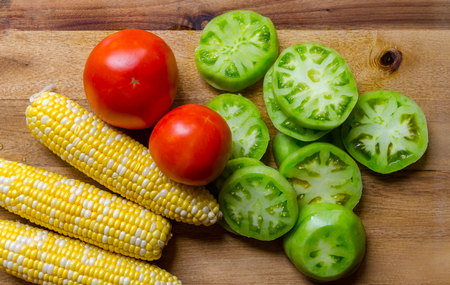 Fresh homegrown organic vegetables including corn, tomato and sliced green tomato. Ripe, juicy and delicious produce ready to prepare for a healthy satisfying nutritious meal. Standard-Bild - 114070582