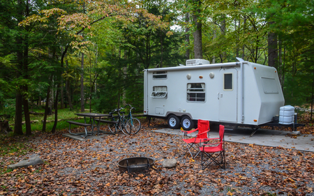 Camping in camper trailer in wooded park camp site with chairs set up around fire pit, and bicycles leaning against picnic table. Standard-Bild - 114070589