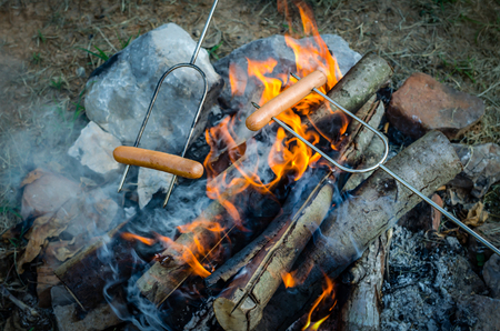 Roasting hotdogs over campfire. Fun and relaxation of preparing food and camping outdoors. Relax and recreation in natures beautiful outdoor setting. Stock Photo