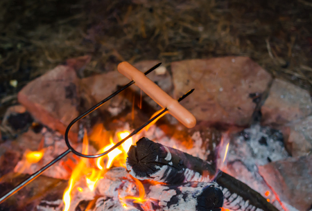 Roasting hot dogs over campfire. Fun and relaxation of preparing food and camping outdoors. Relax and recreation in natures beautiful outdoor setting Standard-Bild - 114070608
