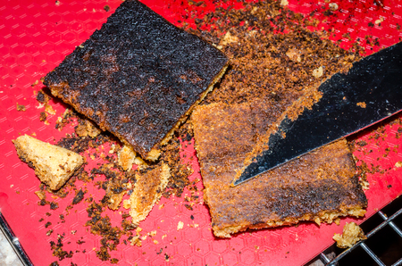 Burned cookie bars. Black overcooked sweet treat. Overdone crust scraped off of one cookie bar, second treat still has burnt bottom intact.