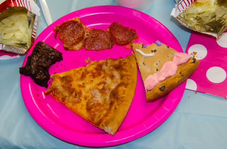 Birthday party food with one bite taken from assorted treats including pizza, chips, cookie cake and brownies. Bright colorful festive party decor of picky eater.  Pizza with pepperoni removed and one bite eaten from each item on the plate.