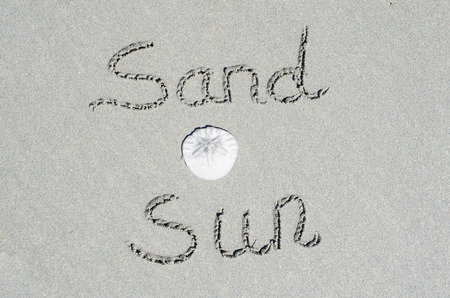 Beach scene of Sand and Sun text with a sand dollar.  Concept of fun and recreational vacation enjoyment at the beach. Celebrate nature and adventure at the ocean. Reklamní fotografie
