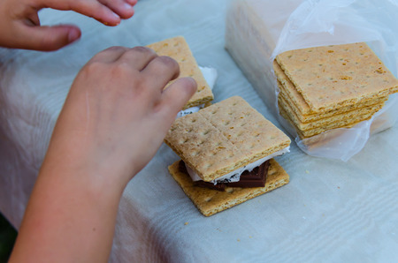 Smore's, a delicious sweet treat with roasted marshmallow, graham cracker and chocolate. Young child's hands making a smore that was fixed outdoors over a campfire while camping. Fun creative eating while traveling and camping