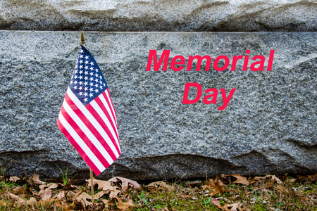 American flag placed in remembrance at Memorial.  Memorial Day text with American flag. National USA Holiday to celebrate Memorial Day.