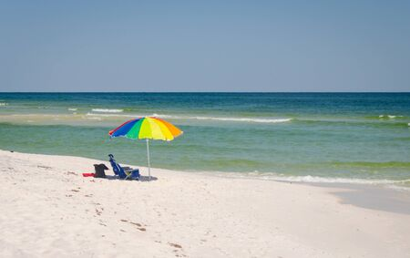 Umbrella and chairs set up at beach shoreline. Beautiful tropical Gulf Coast ocean beach white sands and sea. Vacation tourist travel destination for fun and relaxation