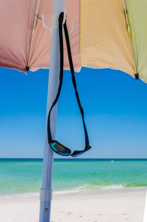 Sunglasses hanging on umbrella, tropical ocean beach shoreline in background.  Beautiful Gulf Coast white sea sand. Vacation tourist travel destination for fun and relaxation.