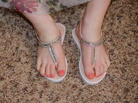 I piedi della ragazza che indossano scarpe scintillanti. Unghie dei piedi del bambino dipinte di rosa. Dita dei piedi del bambino con pedicure che indossa sandali estivi carini.