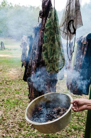 Hunter smoking hunting clothing to create organic scent. Pre-hunt preparation to attempt to mask human scent.