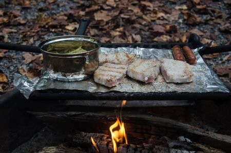 Roasting pork chops and hot dogs  with green beans over open campfire. Fun and relaxation of preparing food outdoors. Relax and recreation in natures beautiful outdoor setting.