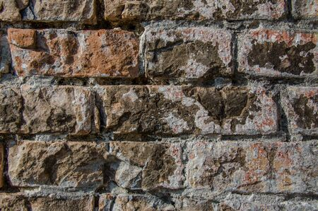 Brick wall, excellent rustic abstract background or backdrop. Color and detail in this beautiful vintage brick wall, built years ago. Cracked and aged surface of textured brick wall.