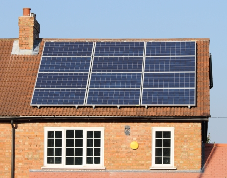 solar equipment: Solar photovoltaic panels on house roof against a blue sky Stock Photo