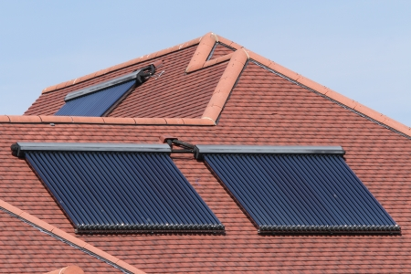 array: Solar glass tube hot water panel array mounted on a tiled roof against a blue sky Stock Photo