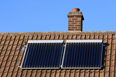 solar heating: Solar glass tube hot water panel array mounted on a tiled roof against a blue sky Stock Photo