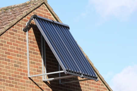 Solar glass tube hot water panel array mounted on a tiled roof against a blue sky photo