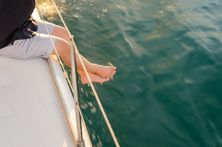 sailboat: Man sit on yacht deck, legs outside of yacht under warm sunset flare Stock Photo