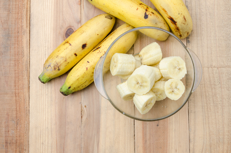 banana: Top view banch of bananas and a sliced banana in a  glass bowl on wood table