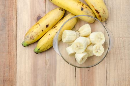 banane: Vue de dessus banch de bananes et une banane en tranches dans un bol en verre sur table en bois