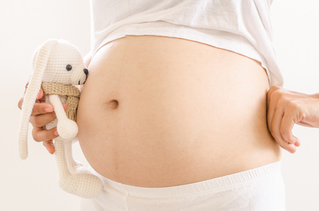 pregnant lady: Close up pregnant women touching her belly with hands Stock Photo