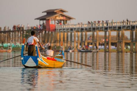 boatman: Unidentified Burmese boatman rowling boat for tourist in front of U Bein wooden bridge