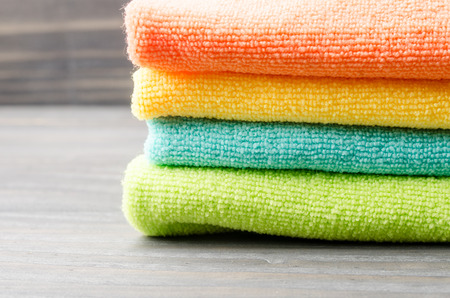 Colorful bath towels on wooden background closeup