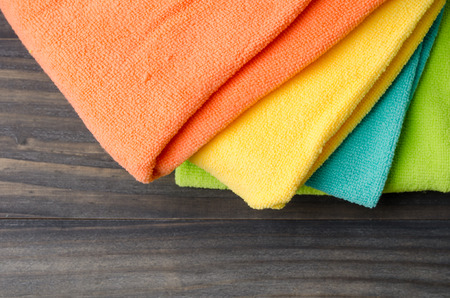 absorb: Colorful bath towels on wooden background closeup