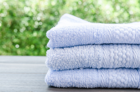 Close up of bath towels on wooden table with light bokeh background