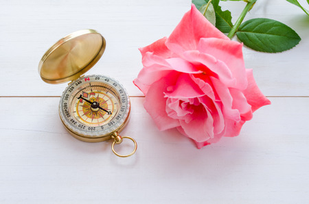 Compass with beautiful pink rose on a white wooden background