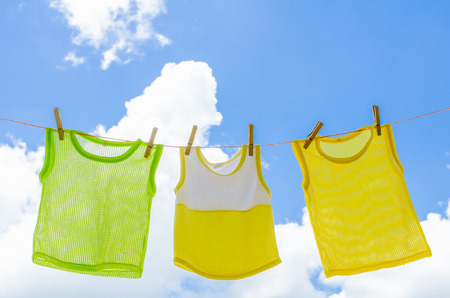 sully: Baby clothes laundry hanging on the clotheline for sun dry after wash over blue sky in sunny day