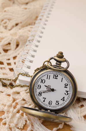 Vintage pocket watch with blank note book on lace background